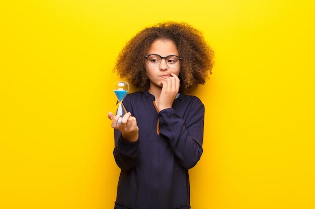 Menina afro-americana contra parede plana, segurando um relógio de areia temporizador