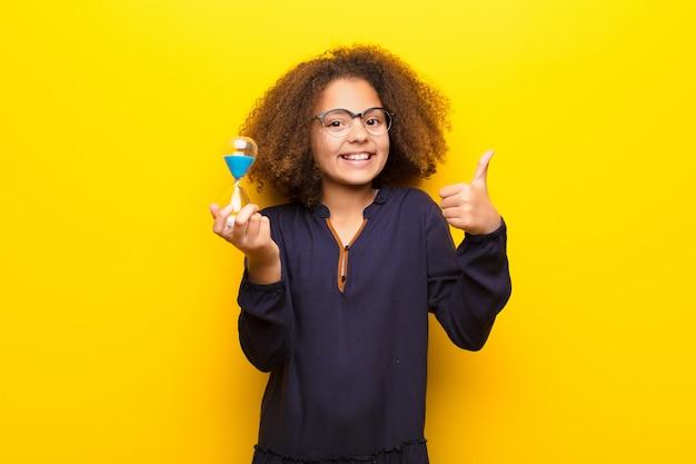 Menina afro-americana contra parede plana, segurando um relógio de areia