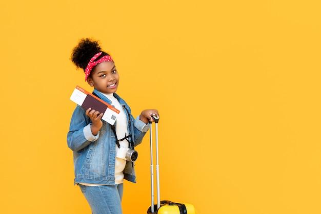Menina afro-americana de viagem com passaporte de bagagem e cartão de embarque isolado na parede amarela com espaço de cópia