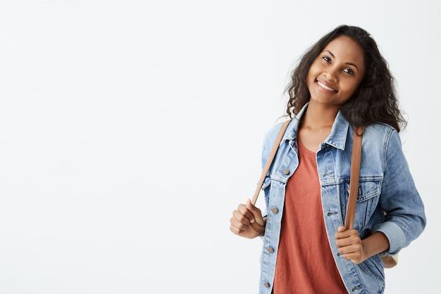 Menina afro-americana elegante com cabelos escuros ondulados se divertindo dentro de casa e com um sorriso alegre. jovem bonita jaqueta jeans sorrindo alegremente mantendo as mãos na mochila