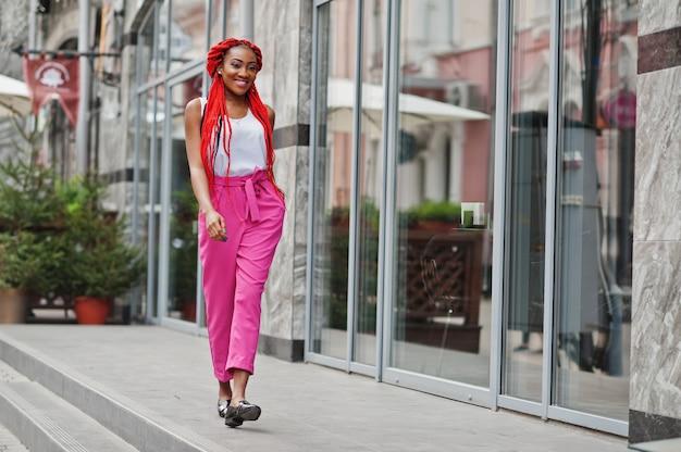 Menina afro-americana elegante em calças cor de rosa e temores vermelhos colocados ao ar livre.