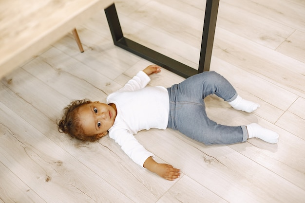 Menina afro-americana encontra-se no chão de madeira, camisa branca, calça azul. criança brincando, se divertindo, brincando na sala