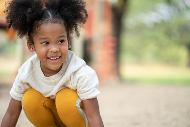 Menina afro-americana feliz sorrindo para o parque infantil no parque
