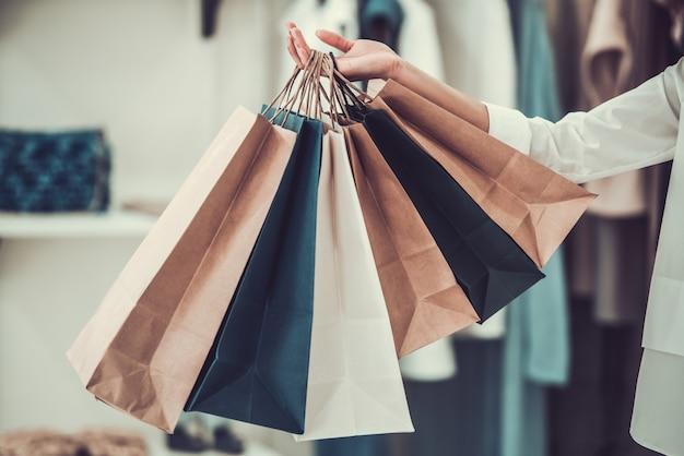 Menina afro-americana segurando sacolas de compras.