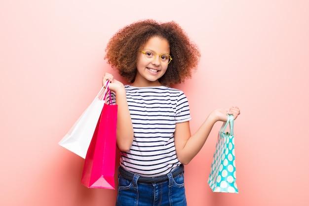 Menina afro-americana sobre parede com sacolas de compras