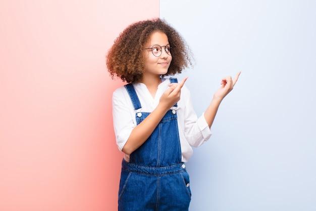 Menina afro-americana sorrindo alegremente e apontando para o lado e para cima com as duas mãos mostrando o objeto no espaço da cópia contra uma parede plana