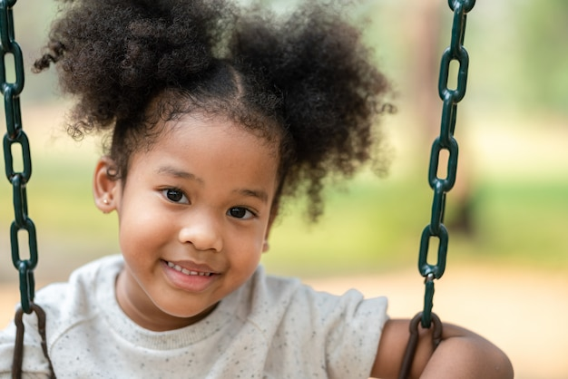 Menina afro-americana, sorrindo, olhar para a câmera no playground no parque