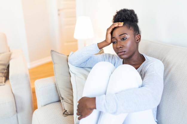 Menina afro-americana triste, pensativa, preocupada, sentada no sofá olhando para longe, sentindo-se deprimida, duvidosa