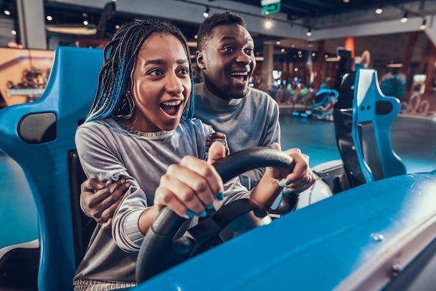 Menina afro-americano do sorriso que monta o carro azul na arcada.