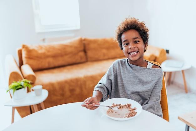 Menina afro-americano lindo que come cereais, olhando a câmera.