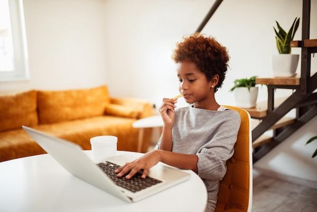 Menina afro-americano pequena bonita que usa o portátil em casa.