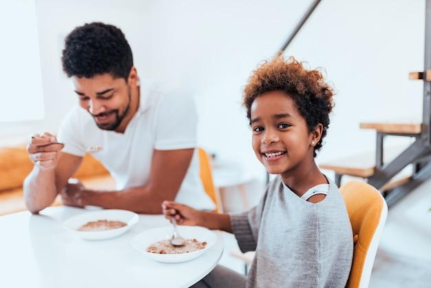 Menina afro-americano pequena bonito que come o café da manhã saudável com seu paizinho.