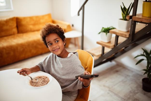 Menina afro-americano pequena bonito que come o café da manhã saudável e que olha a tevê.