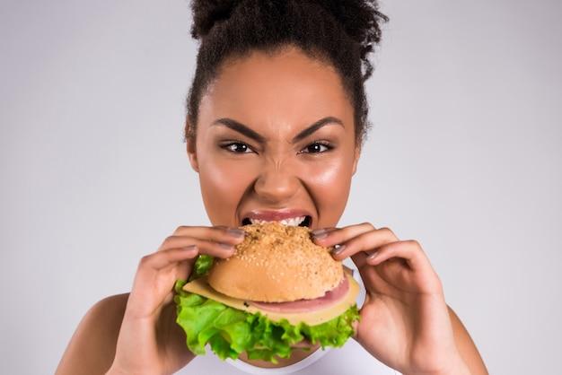 Menina afro-americano que come o hamburger isolado.