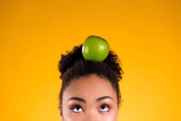Menina afro-americano que mantém a maçã isolada.