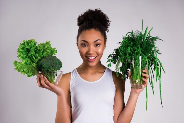 Menina afro-americano que mantém verdes isolados.