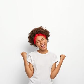 Menina afro feliz e encantada fecha os punhos, sente triunfo, alegra-se com a vitória, mantém os olhos fechados, sorri amplamente, veste uma camiseta branca, fica em pé dentro de casa