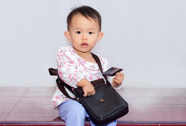 Menina agradável com saco segurando o cartão de crédito para fazer compras no fundo branco