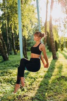 Menina agradável que faz a ioga da mosca na pose de assento ao ar livre.