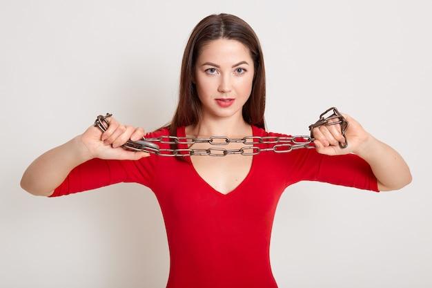 Menina agressiva nova com as correntes nas mãos isoladas sobre o branco