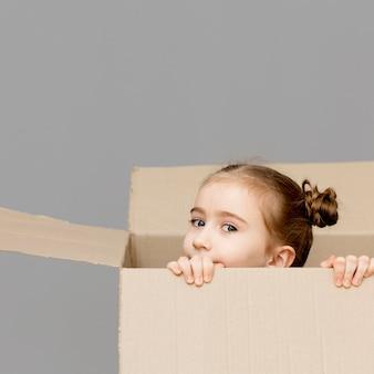 Menina, ajudando a embalar as caixas