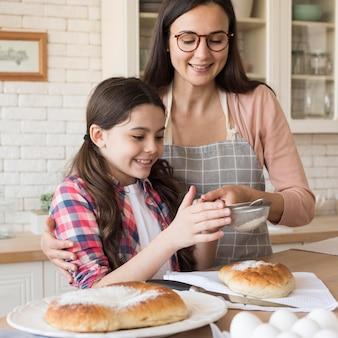 Menina, ajudando a mãe a cozinhar