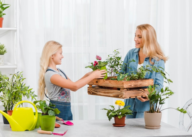 Menina, ajudando a mãe a cuidar de flores