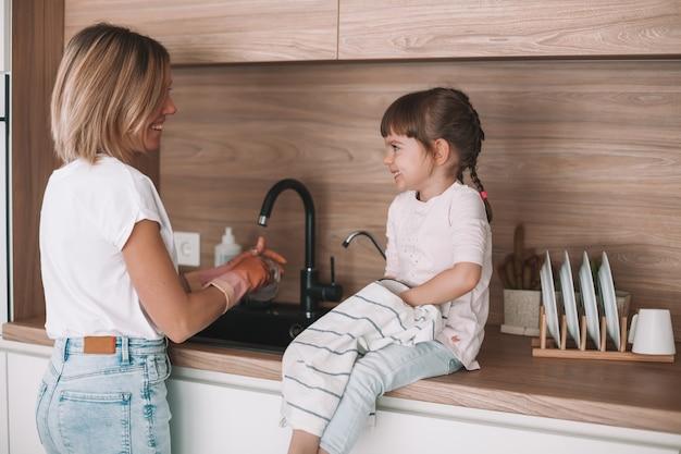 Menina ajudando a mãe a lavar a louça na cozinha