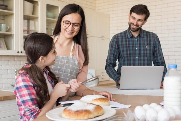 Menina, ajudando os pais a cozinhar