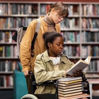 Menina ajudando um colega em cadeira de rodas a escolher um livro para um projeto