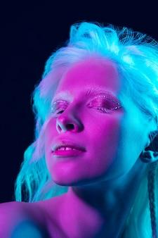 Menina albina com pele branca, lábios naturais e cabelo branco em luz de néon, isolado no fundo preto do estúdio.