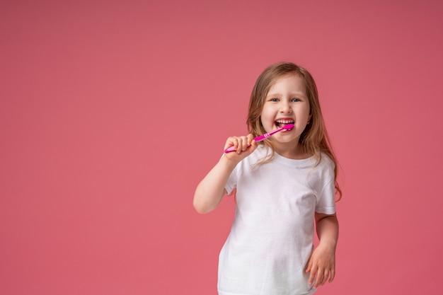 Menina alegre 4 anos ,, sorrindo, escovando os dentes