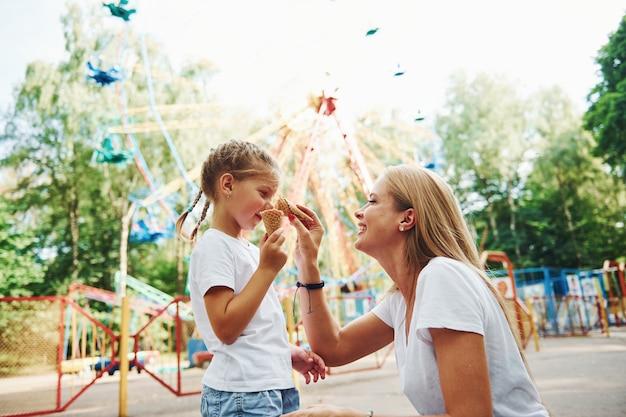 Menina alegre, a mãe dela se divertindo no parque, perto das atrações