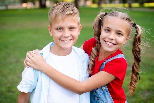 Menina alegre, abraçando o menino no parque
