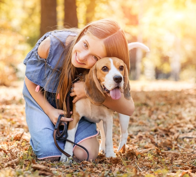 Menina alegre abraçando um cachorro beagle lá fora