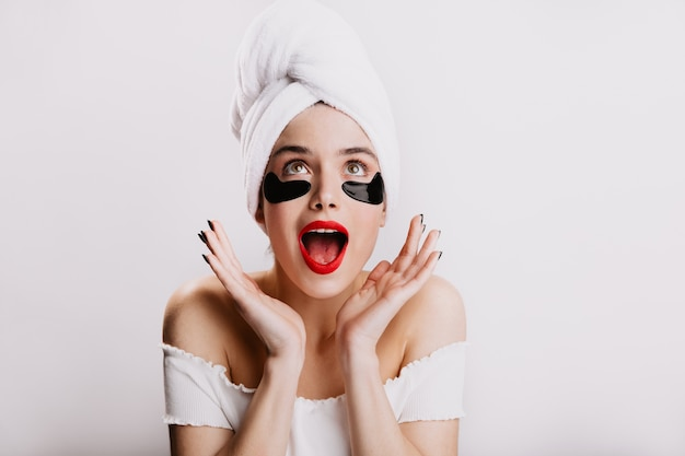 Menina alegre abriu a boca de espanto. instantâneo de mulher após o banho com adesivos hidratantes.