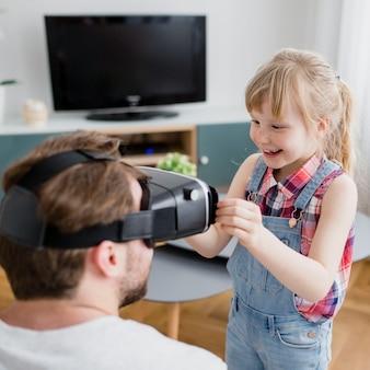 Menina alegre, ajudando o pai com fone de ouvido de vr
