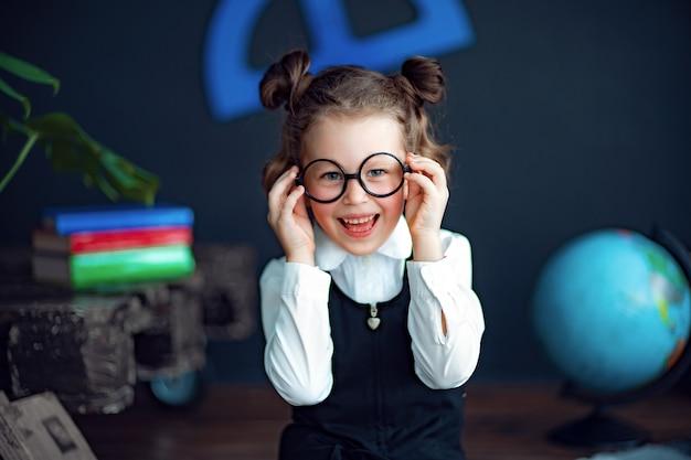 Menina alegre, ajustando os óculos e sorrindo