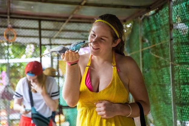 Menina alegre alimenta os papagaios com as mãos e ri em contato com o zoológico
