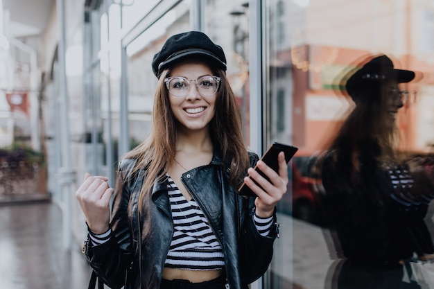Menina alegre andando na rua com jaqueta de couro preta depois da chuva