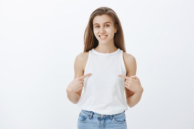Menina alegre apontando para si mesma, quer participar