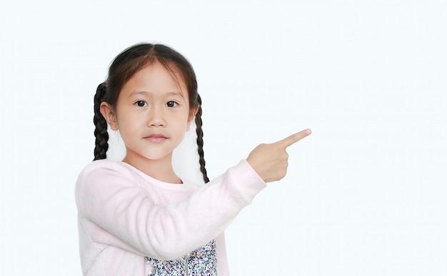 Menina alegre apontar o dedo indicador ao lado para apresentar algo