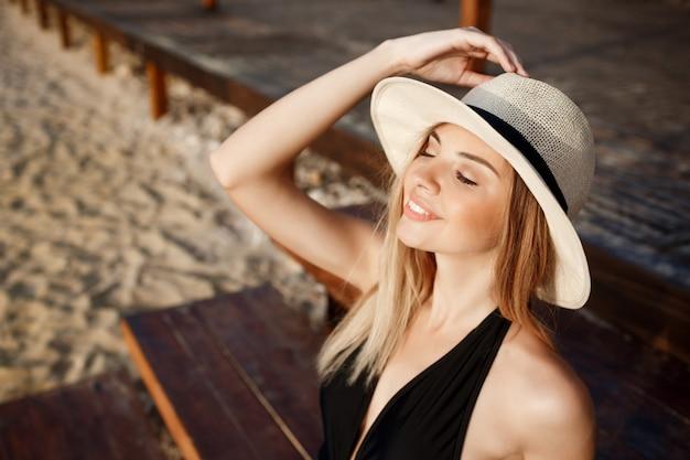 Menina alegre bonita no chapéu baseia-se na praia de manhã
