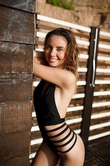 Menina alegre bonita vestida em trajes de banho repousa na praia