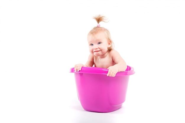 Menina alegre bonitinha na banheira roxa