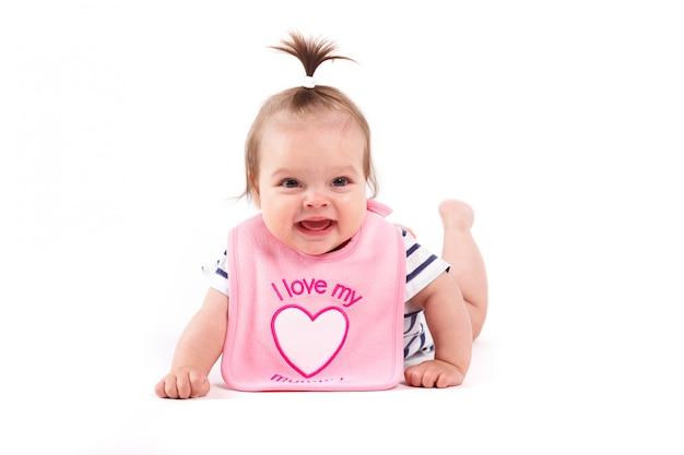 Menina alegre bonito no babador cor-de-rosa