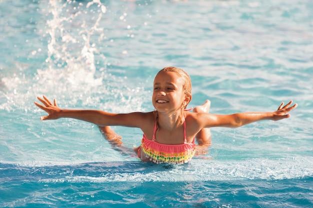 Menina alegre brincando na piscina com águas claras e cristalinas e olhando sorrindo para a câmera