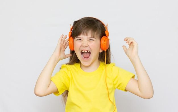 Menina alegre canta em voz alta a música isolada no fundo branco