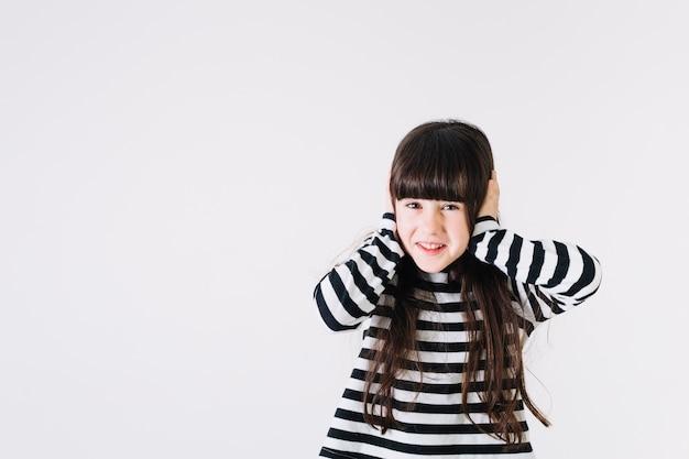 Menina alegre, cobrindo as orelhas