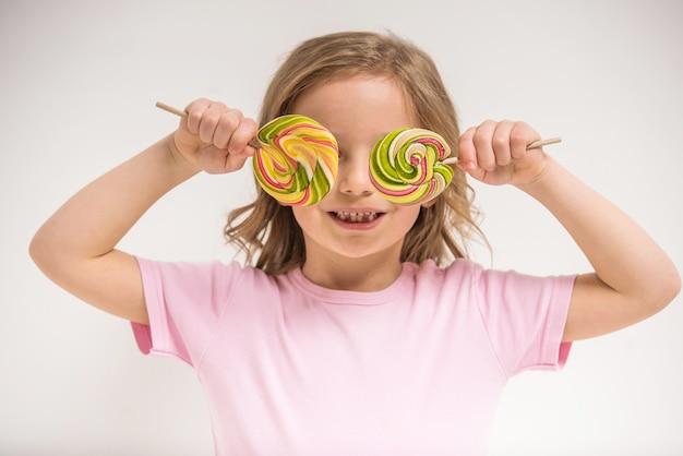 Menina alegre cobrindo os olhos com pirulitos e sorrindo.